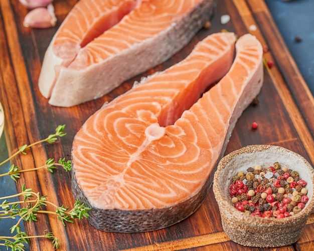 Two salmon steaks, fish fillet, large sliced portions  on a chopping board on dark table