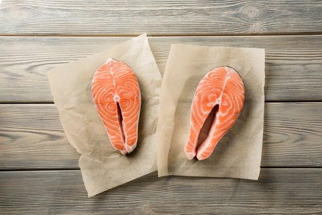 Два стейка лосося на деревянном столе. стейки из красной рыбы, снятые сверху.