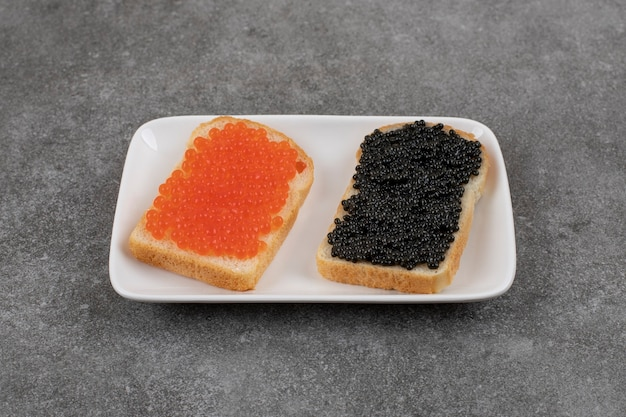 Two sandwich with red and black caviar on white black.