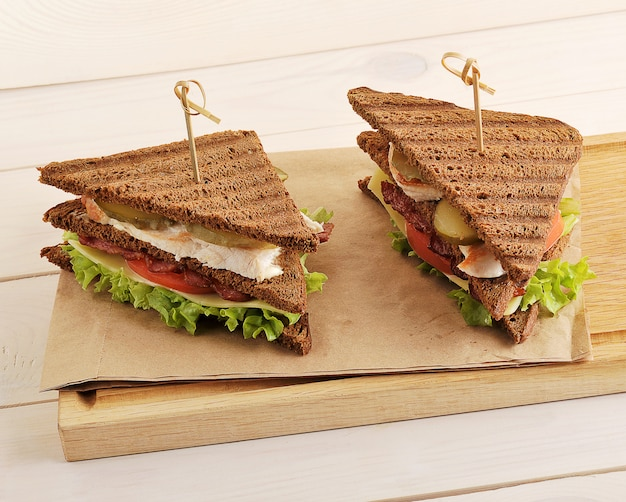 Two sandwiches from triangular pieces of bread with chicken breast