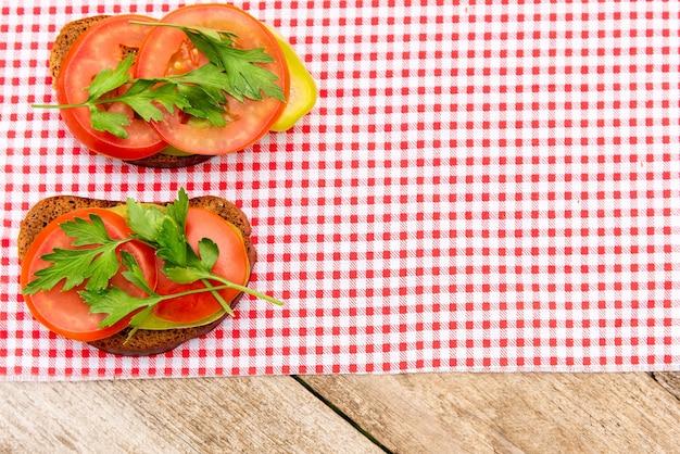 Two sandwiches on red plaid salfetka.