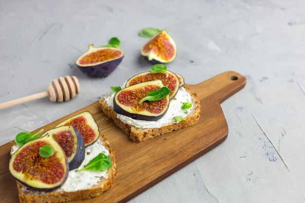 木製の素朴なまな板で提供されるクリームチーズ、イチジク、蜂蜜と葉のサラダと2つのサンドイッチ