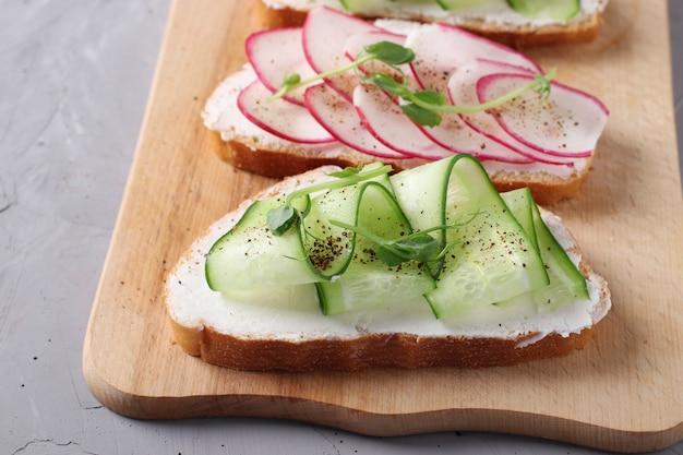Два бутерброда с огурцами, редисом и микрозеленью гороха на деревянной доске на сером фоне бетона, крупным планом
