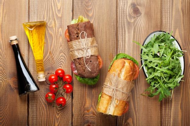 木製のテーブルにサラダ、ハム、チーズ、トマト、サラダ、スパイスのサンドイッチ2つ。コピースペースのある上面図