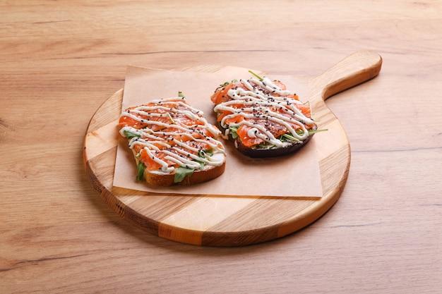 둥근 나무 쟁반에 훈제 연어와 소금에 절인 연어, 아루굴라, 소스를 곁들인 샌드위치 2개.