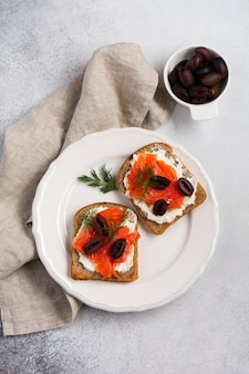 Two sandwiches with smoked pink salmon olives, kalamata, microgreens and cream cheese on gray ceramic plate and trendy concrete table. traditional scandinavian toast. top view.