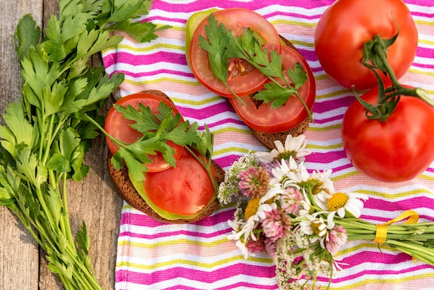 Two sandwiches with tomatoes and herbs.