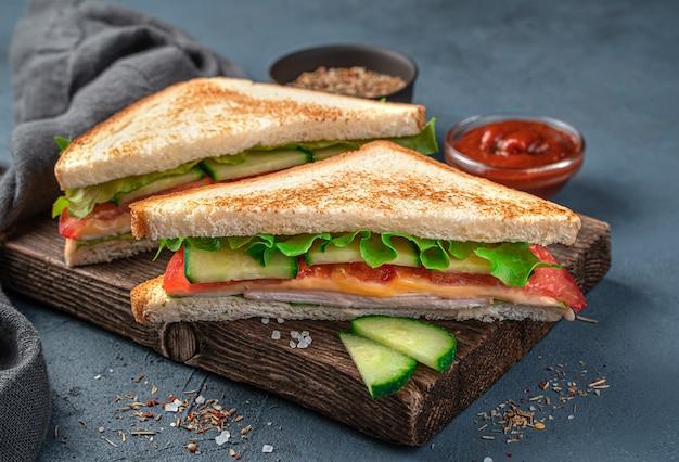 青灰色の背景に野菜、レタス、ハム、チーズの2つのサンドイッチ。側面図、クローズアップ。スペースをコピーします。