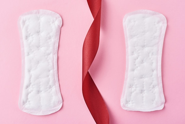 Two sanitary pads and red ribbon