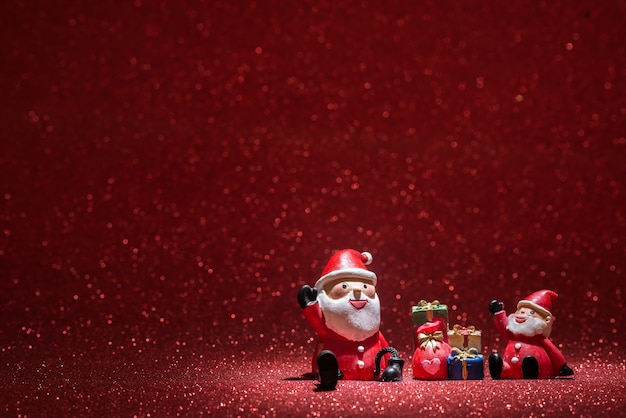 Two santa claus with shiny red background