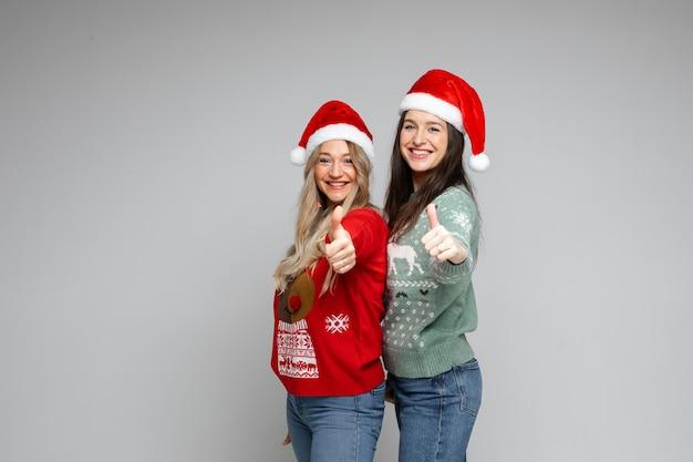 赤い帽子をかぶった2人のサンタの女の子は、クリスマスと新年の広告のためのコピースペースで灰色の背景に親指を立てるジェスチャーを示しています