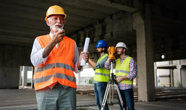 두 명의 만족스러운 엔지니어, 건축가가 배경에 건설 구조를 가진 건물 현장에서 이야기하고 있습니다.