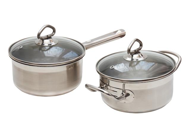 白い背景の上の長いハンドル、カバー付きのステンレス鋼で作られた2つの鍋。孤立