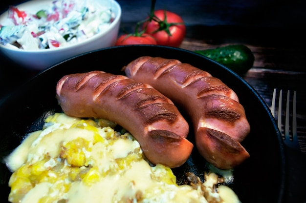 Two sausages scrambled eggs and salad on a wooden table