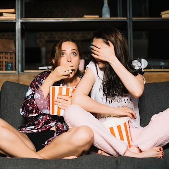 Two scared female friends eating popcorn while watching television