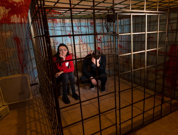 Two scared halloween victims imprisoned in a metal cage with a blood splattered wall behind them sitting in terror awaiting their fate