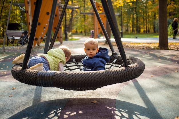 두 명의 겁에 질린 유아 소년과 소녀가 무인 상태로 가을 공원의 놀이터에 있는 그네 해먹에 앉아 있습니다.