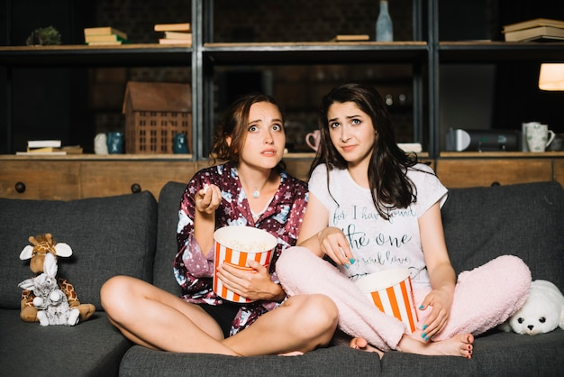 Two scared women sitting on sofa with popcorn watching television