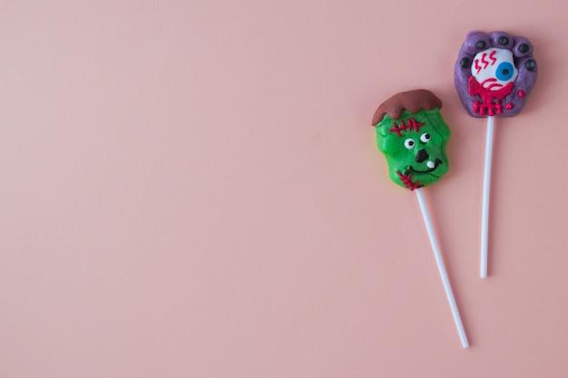 두 개의 무서운 heluin 막대 사탕이 분홍색 배경에 놓여 있습니다.