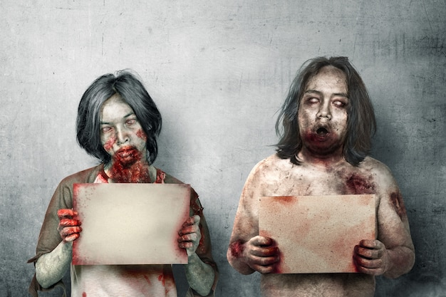 Two scary zombies with blood and wound on his body holding a signboard