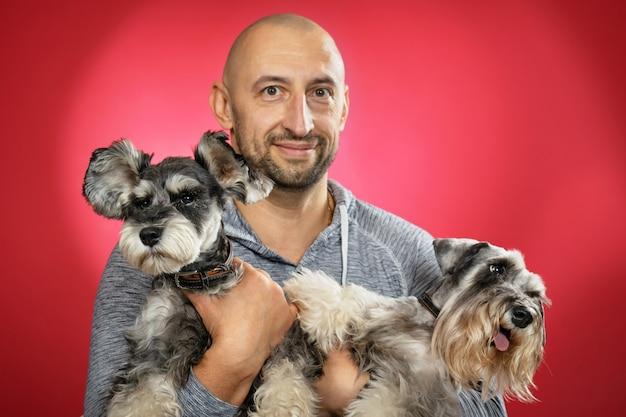 Две собаки шнауцера в руках улыбающегося человека