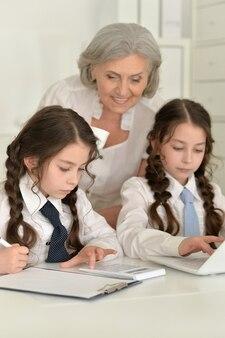 할머니와 숙제를 하는 두 여학생