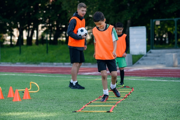 Two school boys are running ladder drills on during football summer camp.