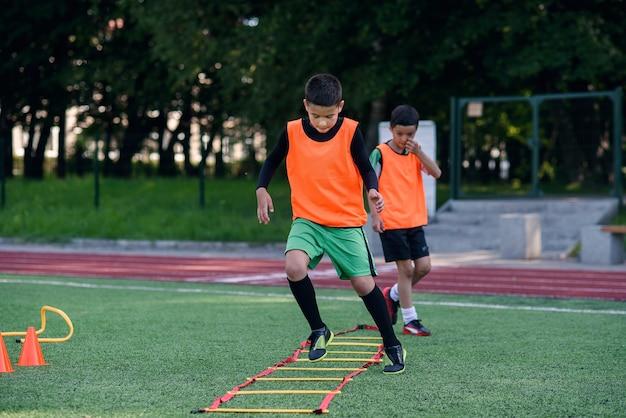Два школьника бегают по лестнице на тренировке по футболу