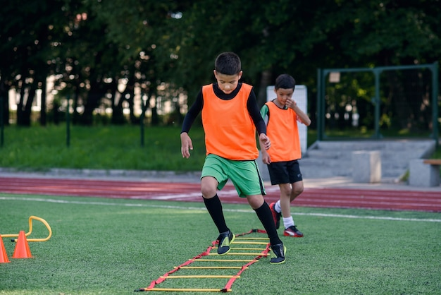 Two school boys are running ladder drills on soccer training