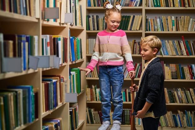두 명의 학교 아이들이 서로 돕고 선반에서 책을 꺼내고 서서 이야기하고 도서관에서