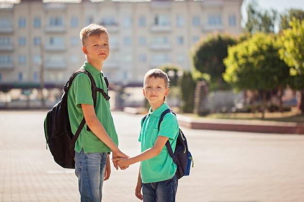Два школьника детские мальчики с рюкзаком в солнечный день. счастливые дети ходят в школу.