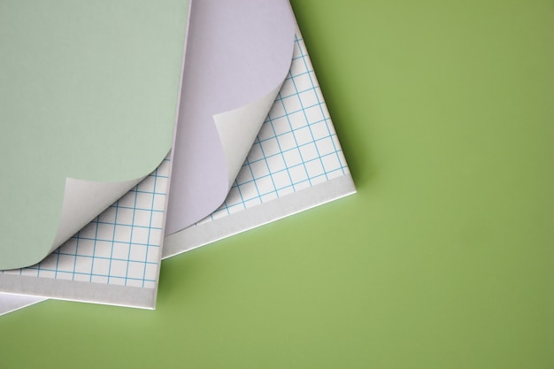 Two school notebooks on a green background.
