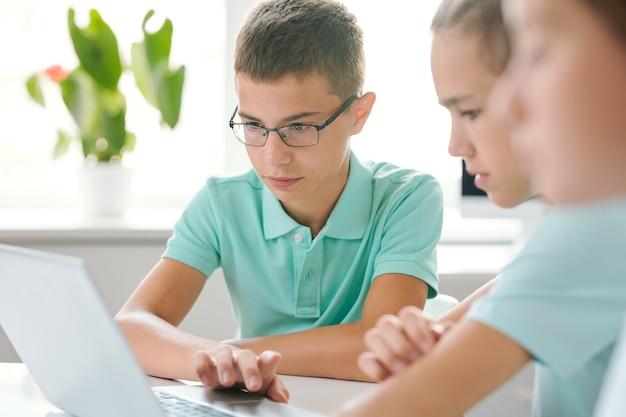 Два школьника сосредоточились на школьной работе, сидя перед ноутбуком и просматривая онлайн-информацию