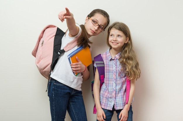 Two schoolchildren stand with backpacks