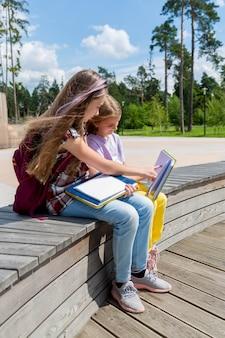 Две школьницы сидят на скамейке в общественном парке, делают домашнее задание и читают книгу