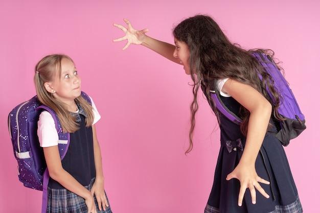 Две школьницы в школьной форме дерутся на розовом фоне.