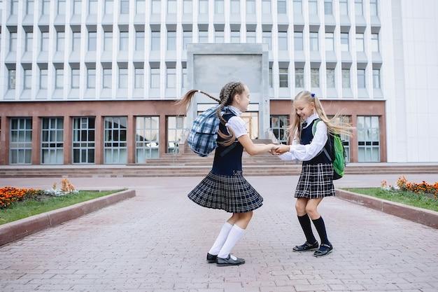 제복을 입은 두 여학생이 만나 학교 앞에서 껴안고 서 있습니다.