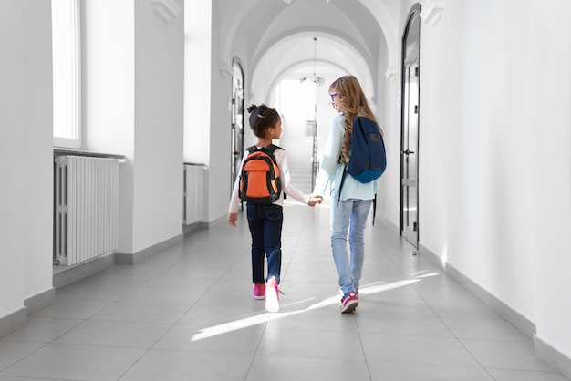 Two schoolgirls in jeans and sneakers with backpacks walking in long light hallway after lessons.
