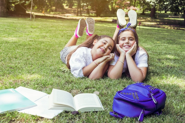 Two schoolgirls lying on grass with heads propped in hands smiling