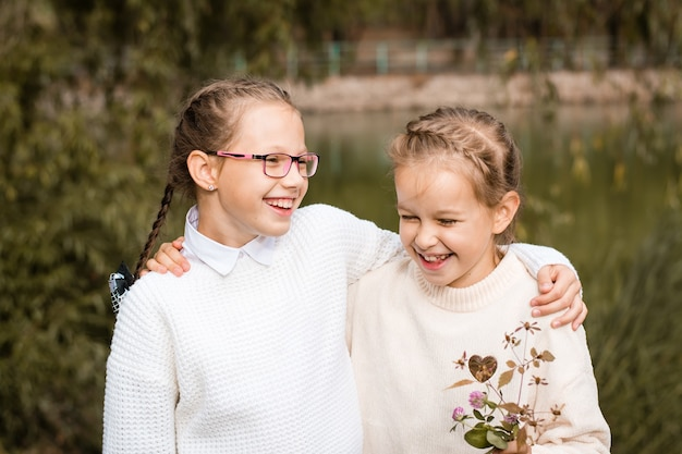 Two schoolgirls walk, hug and laugh after school in the park. back to school concept