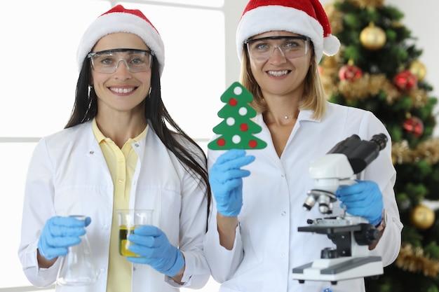 2人の科学者がクリスマスツリーを背景にフラスコと顕微鏡を持っています。科学者とクリスマスのコンセプト