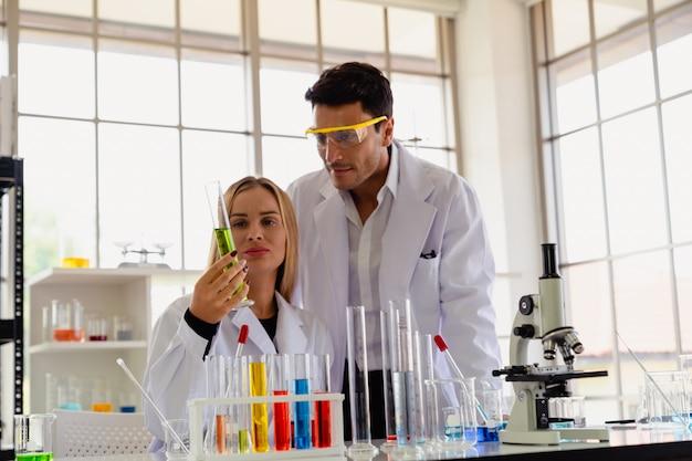 Ученый 2 смотря стеклянную пробирку пока делающ исследование в научной лаборатории