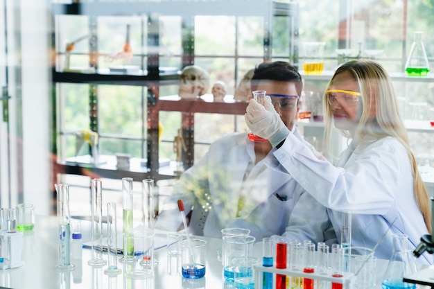 Two scientist looking at medical testing result in glass tube while doing research in science laboratory
