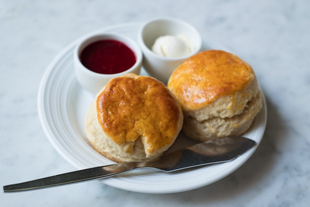 Two scone with strawberry jam and cream cheese sauce