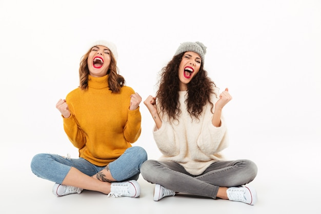 Two screaming girls in sweaters and hats sitting on the floor together and rejoices over white wall
