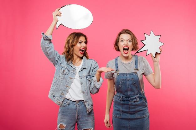 Two screaming women friends holding speech bubbles.