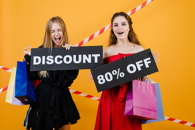 Two screaming women have discount 80% off sign with colorful shopping bags and signal tape isolated over yellow