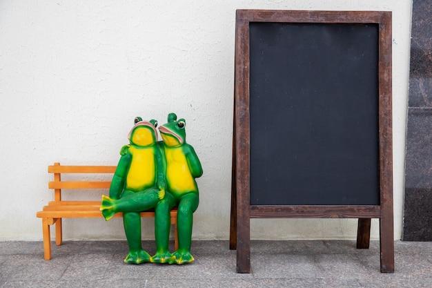 カエルの2つの彫刻がベンチに座って抱きしめます