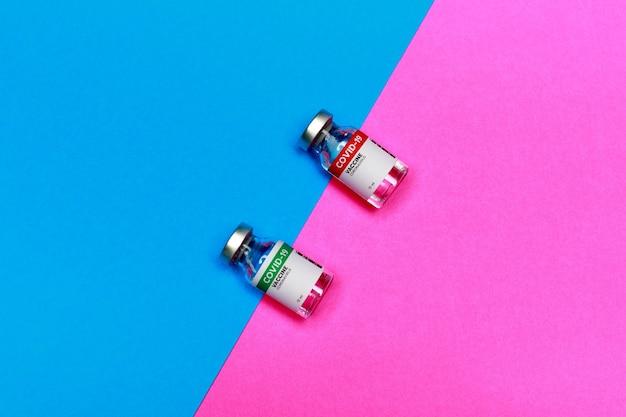 Две запечатанные стеклянные капсулы с вакциной covid-19 между границей синей и розовой заштрихованной фоновой зоны выглядят как зона вспышки вируса или заболевания против вакцинации или иммунитета.