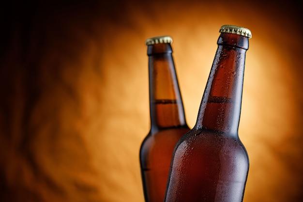 ラベルの付いていない2本の氷で冷やしたビールのボトルを、テクスチャーの素朴な茶色の背景の上にハイライトし、ビネットをクローズアップ